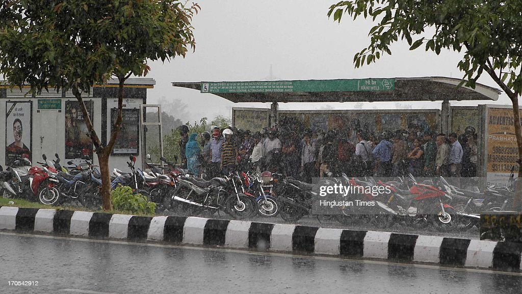 People take shelter in bus stand during the heavy pre monsoon rain on June 14, 2013 in New Delhi, India. The city received 11.6 mm rainfall and the humidity oscillated between 47 and 91 percent.
