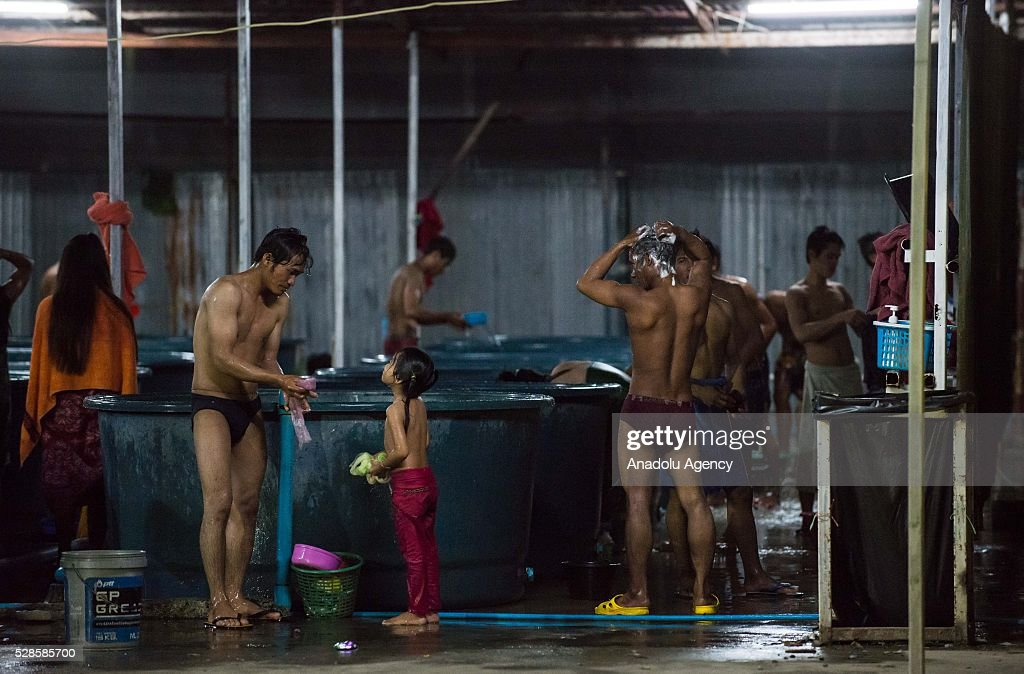 People take shower in a bathhouse at a construction workers' camp on May 6, 2016 in Bangkok, Thailand. Mainly migrants from neighboring countries, like Cambodia and Laos, live in this camp, which has grocery shops, a common washing area and even a small school, on the outskirts of Bangkok.