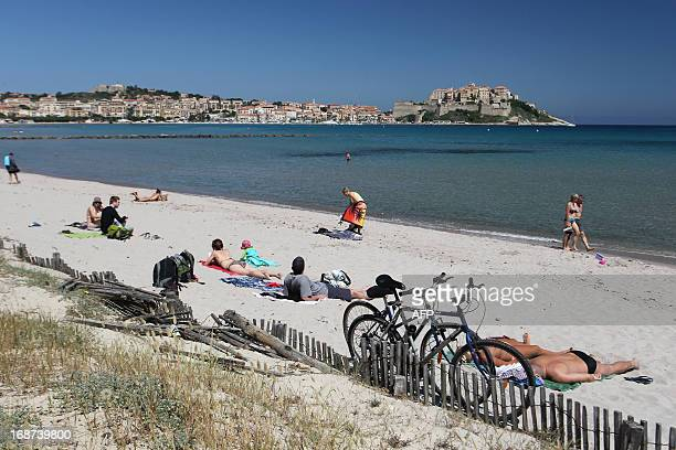 People take sun bath on the beach with the olod city of Calvi in the bckground on May 14 French Mediterranean Island of Corsica AFP PHOTO / PASCAL...