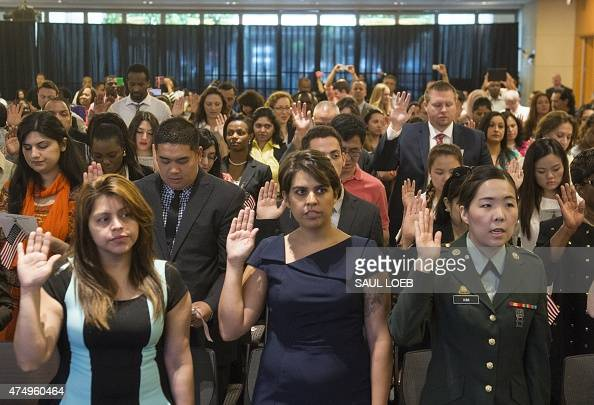 People take the citizenship oath as they become US citizens during a naturalization ceremony at the US Patent and Trademark Office in Alexandria...