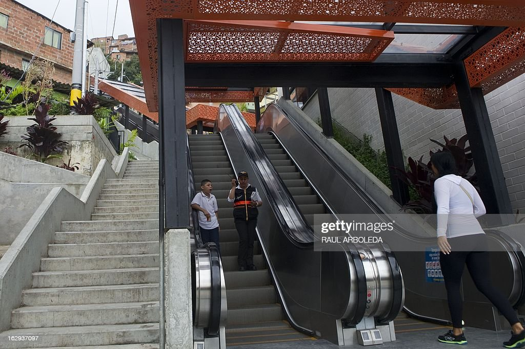 "People take the escalators at Comuna 13 neighbourhood, one of the poorest and most violent areas of the northeastern Colombian city of Medellin, Antioquia department, Colombia on March 1, 2013. Medellin, which competed with New York and Tel Aviv, was chosen by popular vote through the internet, as the ""Innovative City of the Year"" during the City of the Year contest, organized by The Wall Street Journal and Citigroup. The distinction was basically made for its modern transportation system, its public library, escalators built in a shantytown and schools that have allowed the integration of society. AFP PHOTO/Raul ARBOLEDA"