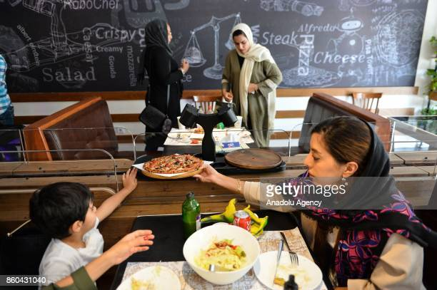 People take their food served by robot waiter which moves on rail system placed between tables at the first robotic restaurant 'RoboChef' in Tehran...