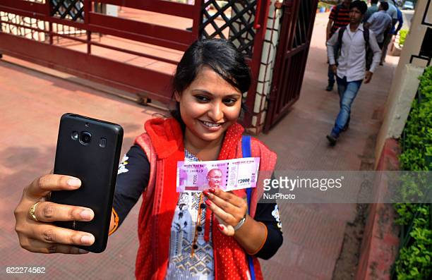 People takes a selfie and shows the new 2000 rupees note after get it in exchange discontinued currency notes at the Reserve Bank of India in the...