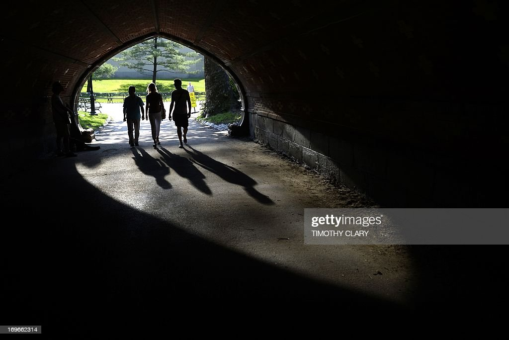 People takes advantage of the hot weather as they walk through a tunnel near the Belvedere Castle in Central Park on May 30, 2013 as temperatures were expected to reach in the 90's (30C) in New York City. AFP PHOTO / TIMOTHY CLARY