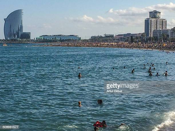 People taking bath on the beach of Barceloneta in Barcelona's city with the Hotel W on the background