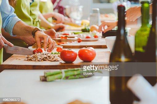 Personas que toman parte en clases de cocina, recorte de las verduras