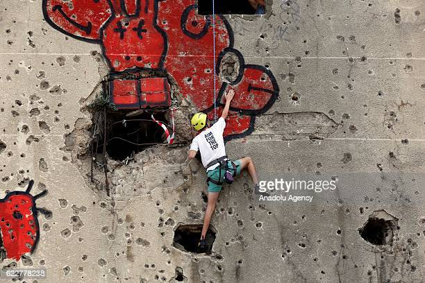 People taking part in the competition held in the Bishara El Huri region of the capital Beirut try to climb the entire wall using holes created in...