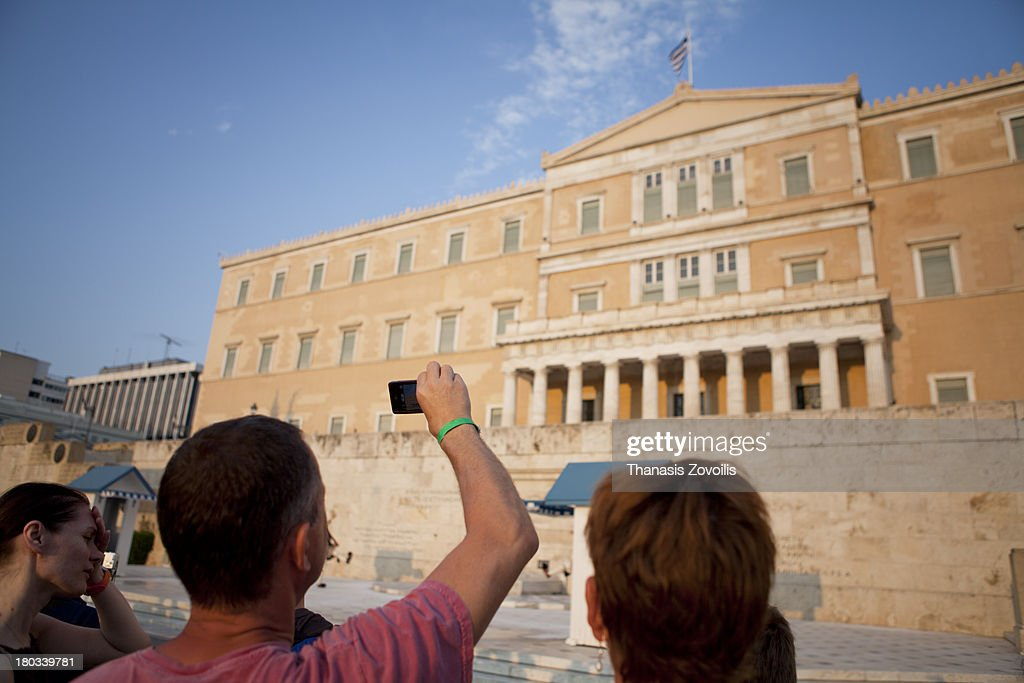 CONTENT] People taking pictures of Greek Evzones in summer service uniform changing guards at the tomb of the unknown soldier on 10 August 2013 in Athens, Greece.The Evzones, or Evzoni, is the name of several historical elite light infantry and mountain units of the Greek Army. Today, it refers to the members of the Presidential Guard , an elite ceremonial unit that guards the Greek Tomb of the Unknown Soldier , the Presidential Mansion and the gate of Evzones camp in Athens. The Evzones are also known, colloquially, as Tsoliades.Evzones on duty perform their movements in a very slow and highly stylized manner. They switch positions with each other every fifteen minutes and remain completely motionless and at attention in the meantime. Since the Guards are required to be totally still at all times, there is one Evzone in normal fatigues uniform and police surveillance to ensure that no one approaches or harasses the Guards while on duty. The 'little changes' take place every hour on the hour, and involve the two incoming and two outgoing sentries, and a supervising 'Corporal of the Change'. The Grand Change takes place at 11 am on Sunday mornings, and involves the whole Guard with its officers and a military band, all marching from the Guard Barracks to the Tomb for the Change, and back. The Grand Change is a popular Sunday morning spectacle for Athenians and tourists alike.