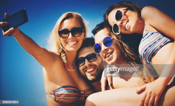 Personnes prenant selfies sur la plage.