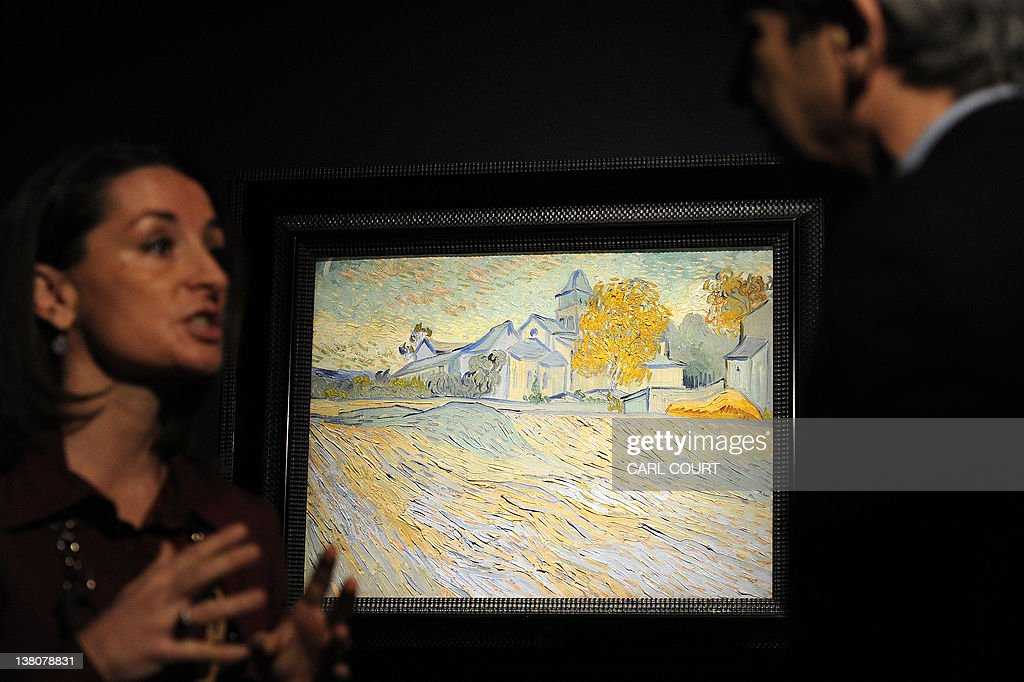 People talk in front of an 1889 painting by Dutch painter Vincent Van Gogh entitled 'Vue de l'Asile et de la Chapelle de Saint-Remy' during a press preview prior to the 'Impressionist and Modern Art Sale' at Christie's auction house in central London on February 2, 2012. From the collection of late actress Elizabeth Taylor, it will come under the hammer on February 7, 2012 and is expected to fetch between 5 - 7million British pounds (7.6 - 11 million US dollars, 5.7 - 7.9 million euros). AFP PHOTO / CARL COURT