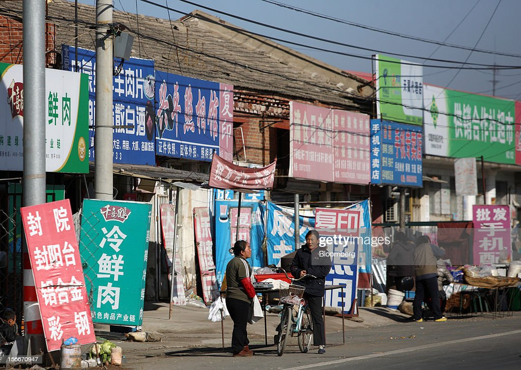 People talk in front of stores in Pinggu, on the outskirts of Beijing, China, on Saturday, Nov. 17, 2012. China's gross domestic product slowed to 7.4 percent in the July-September period from a year earlier, the weakest in three years. Photographer: Tomohiro Ohsumi/Bloomberg via Getty Images