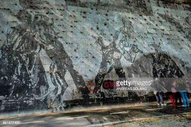 People talk near graffiti painted on the 'Triumphs and Laments' fresco which was completed along the banks of Romes Tiber river less than a year ago...