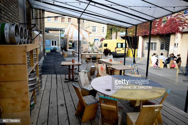 People talk on a table at the bar of 'Les Grands Voisins' site in Paris on October 18 2017 Former SaintVincentdePaul Hospital Les Grands Voisins is a...