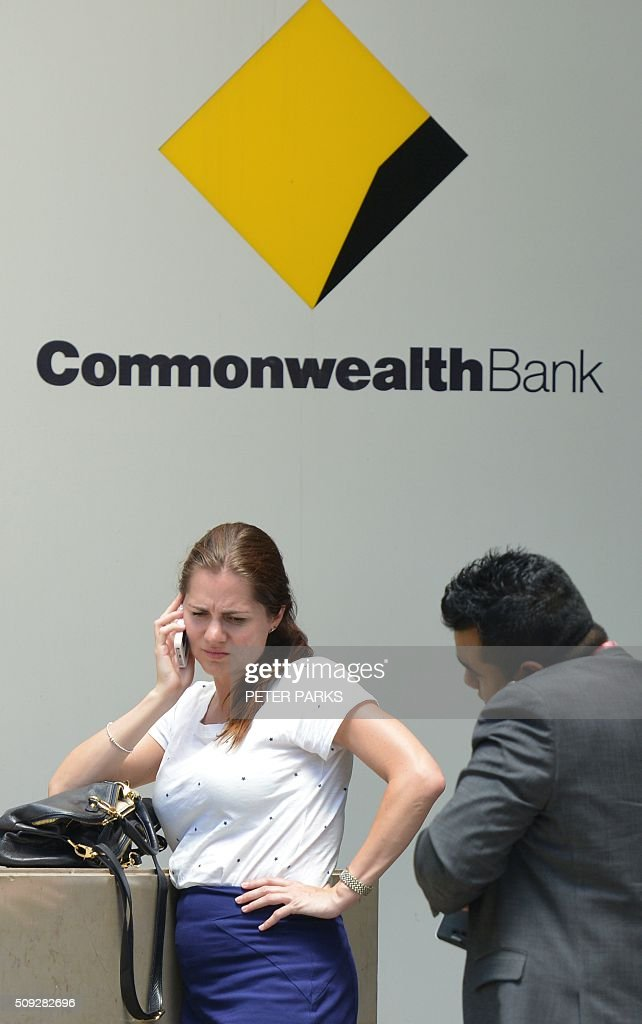 People talk on their phones outside the Commonwealth Bank headquarters in Sydney on February 10, 2016. Australia's biggest company Commonwealth Bank posted a modest two percent rise in first-half net profit to 3.26 billion USD with the lender confident it is well placed to ride out global instability. AFP PHOTO / Peter PARKS / AFP / PETER PARKS