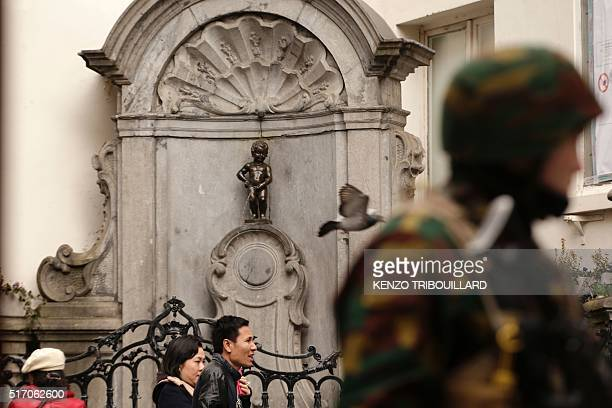 People talk past a soldier standing guard near the Manneken Pis in Brussels on March 23 a day after blasts hit the Belgian capital World leaders...