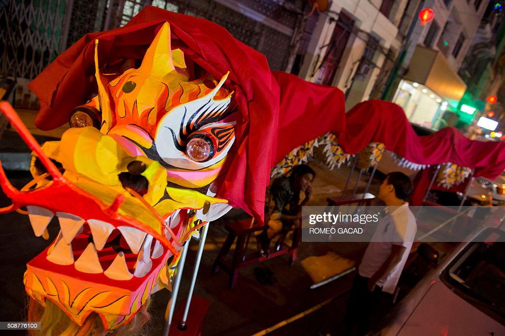 People talk under a dragon effigy in Yangon's Chinatown district on February 6, 2016 in preparation for the Lunar New Year celebrations which falls on February 8 and will mark the start of the year of the monkey. / AFP / ROMEO GACAD