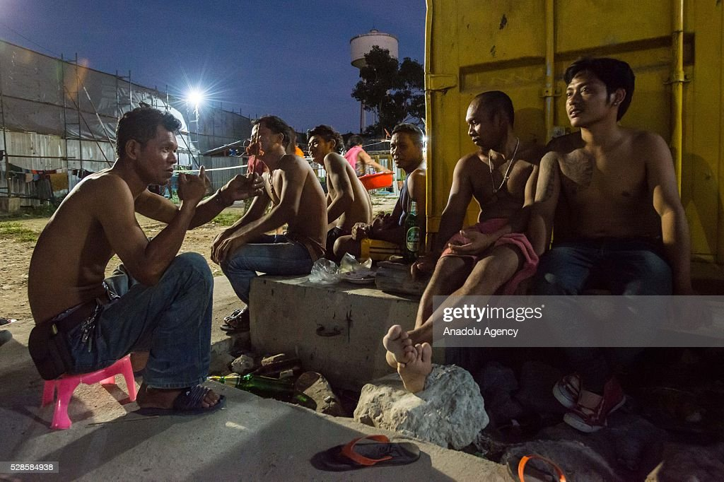 People talk with each other at a construction workers' camp on May 6, 2016 in Bangkok, Thailand. Mainly migrants from neighboring countries, like Cambodia and Laos, live in this camp, which has grocery shops, a common washing area and even a small school, on the outskirts of Bangkok.
