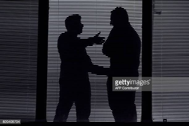 People talking are silhouetted against a window of the Sao Paulo Museum of Art in Sao Paulo Brazil on July 21 2017 / AFP PHOTO / NELSON ALMEIDA