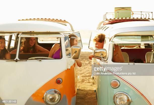People talking in vans on beach