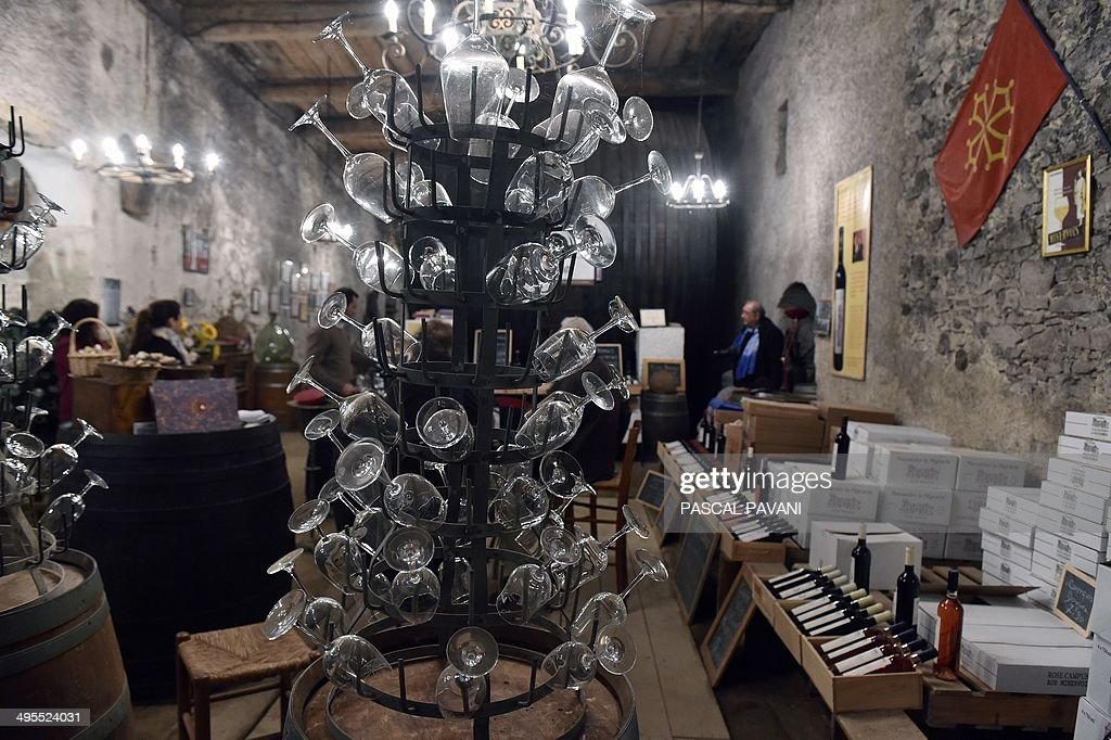 People taste a blend of grapes from the ' Domus-Maximus' Chateau Massamier La Mignarde wineyard in the cellar of the domain in Pepieux southwestern France, on May 21, 2014 .