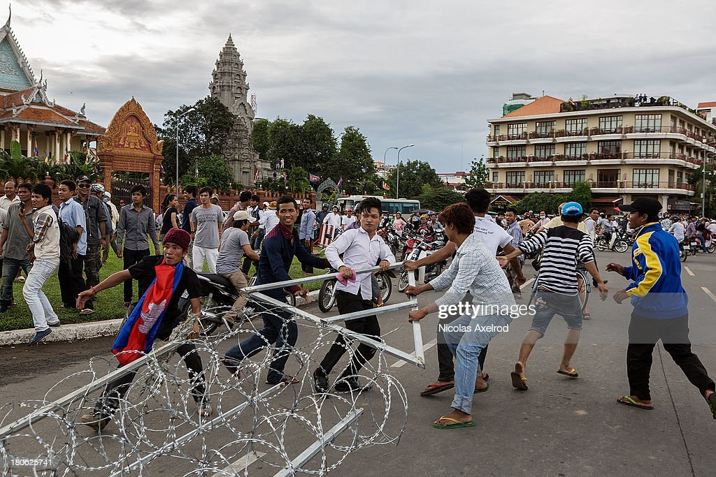 People tear down razor wire barricades as clashes erupt near the riverside on September 15, 2013 in Phnom Penh, Cambodia. The CNRP plan a three day demonstration to contest the Cambodian national election results.