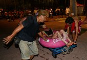 People tend to an injured woman at the Formosa Fun Coast amusement park after an explosion in the Pali district of New Taipei City on June 27 2015...