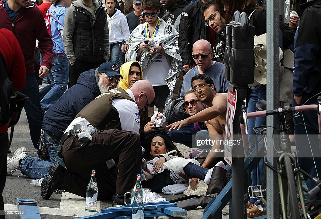 People tend to an injured woman on the corner of Exeter and Newbury Streets after two explosions went off near the finish line of the 117th Boston Marathon on April 15, 2013.