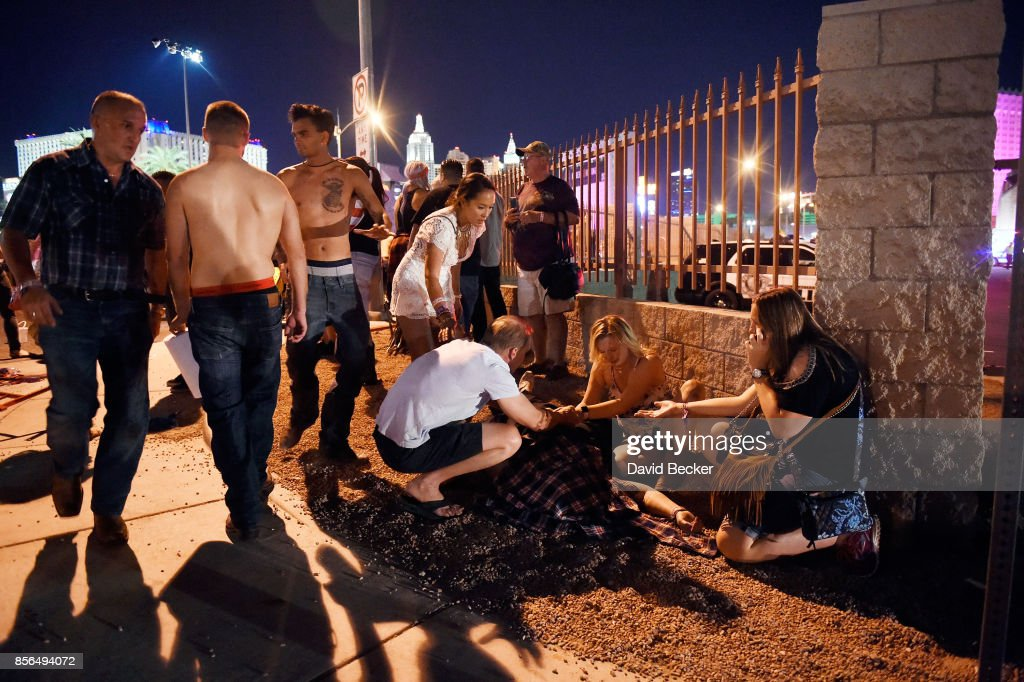 People tend to the wounded outside the Route 91 Harvest Country music festival grounds after an apparent shooting on October 1, 2017 in Las Vegas, Nevada. There are reports of an active shooter around the Mandalay Bay Resort and Casino.
