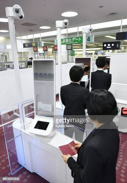 People test a facial recognition machine during a demonstration of the new immigration control system at Haneda airport in Tokyo on Oct 13 2017 The...