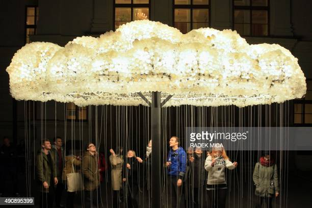 People test a piece of art named 'Cloud' entirely made of light bulbs by Canadian duo of artists Caitlind Brown and Wayne Garrett on May 15 2014 in a...