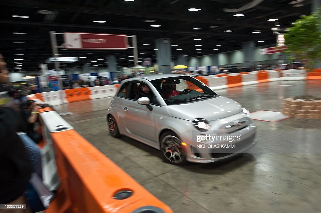 People test drive a Fiat 500 at the Washington Auto Show at the Walter E. Washington Convention Center in Washington on February 2, 2013. The show runs February 1-10. AFP PHOTO/Nicholas KAMM