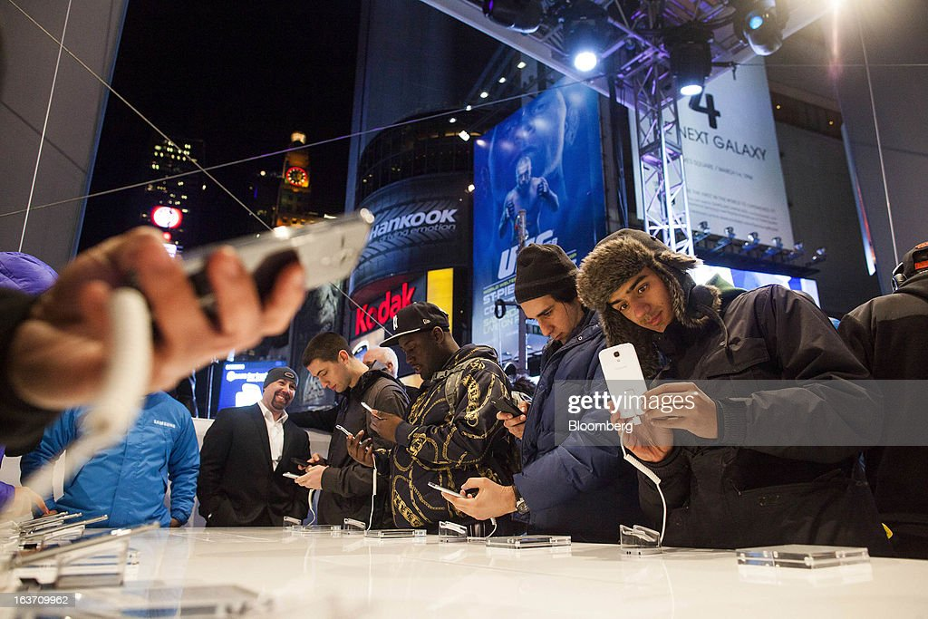 People test out Samsung Electronics Co. Galaxy S4 smartphones during the Galaxy S4's release in Times Square in New York, U.S., on Thursday, March 14, 2013. Samsung Electronics Co. unveiled the Galaxy S4 with a bigger screen and software that tracks eye movements as the world's biggest smartphone seller takes its battle with Apple Inc. to the iPhone maker's home market. Photographer: Michael Nagle/Bloomberg via Getty Images