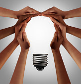 People thinking together as a diverse group coming together joining hands into the shape of an inspirational light bulb as a community support metaphor with 3D elements.