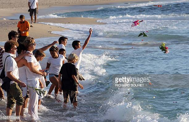 People throw flowers in the sea as part of a ceremony to pay tribune to late bodyboard champion Mathieu Schiller who was attacked by a shark on...