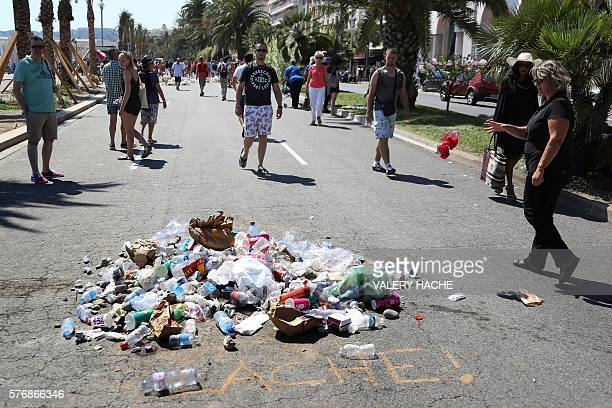 TOPSHOT People throw garbage on July 18 2016 on the Promenade des Anglais seafront in Nice at the site where Mohamed LahouaiejBouhlel a 31yearold...
