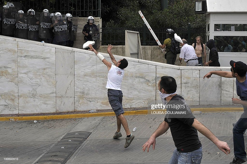 People throw object towards policemen protecting the Greek parliament during a massive demonstration on May 5, 2010 in Athens.Three people were killed in a firebomb attack on a bank in central Athens on May 5 and around 20 people were evacuated from the building.