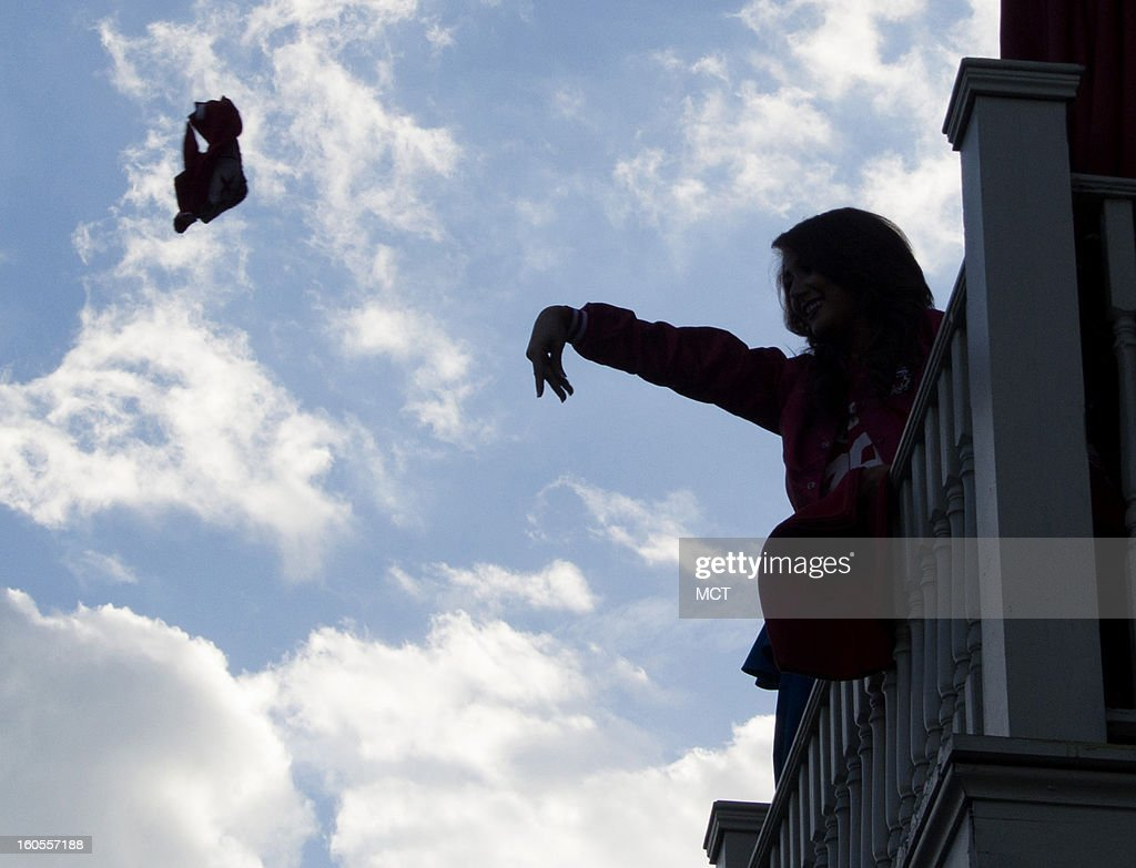 People throw San Francisco 49ers towels and beads to fans from a balcony in New Orleans, Louisiana, on Saturday, February 2, 2013, in advance of Super Bowl XLVII between the 49ers and Baltimore Ravens.