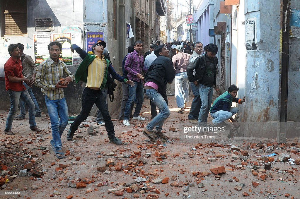 People throw stones during sectarian clashes between Shia and Sunni groups on February 6, 2012 in old city area of Lucknow, India. The violence broke out between the two Muslim sects after Milad un Nabi processions to mark the birthday of the Prophet Muhammad.