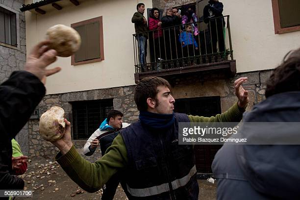 People throw turnips at the Jarramplas as he makes his way through the streets beating his drum during the Jarramplas Festival on January 20 2016 in...