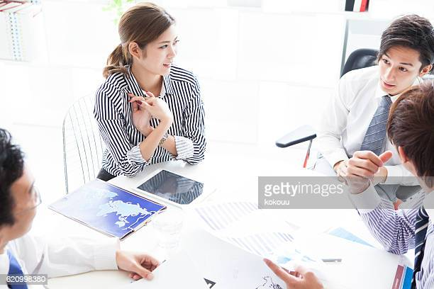 People to meeting while looking at graph in modern office