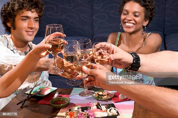 People toasting wine at dinner party