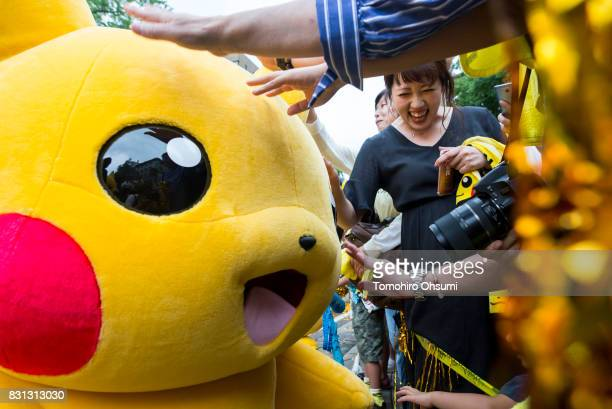 People touch a performer dressed as Pikachu a character from Pokemon series game titles during a parade held as part of the Pikachu Outbreak event...