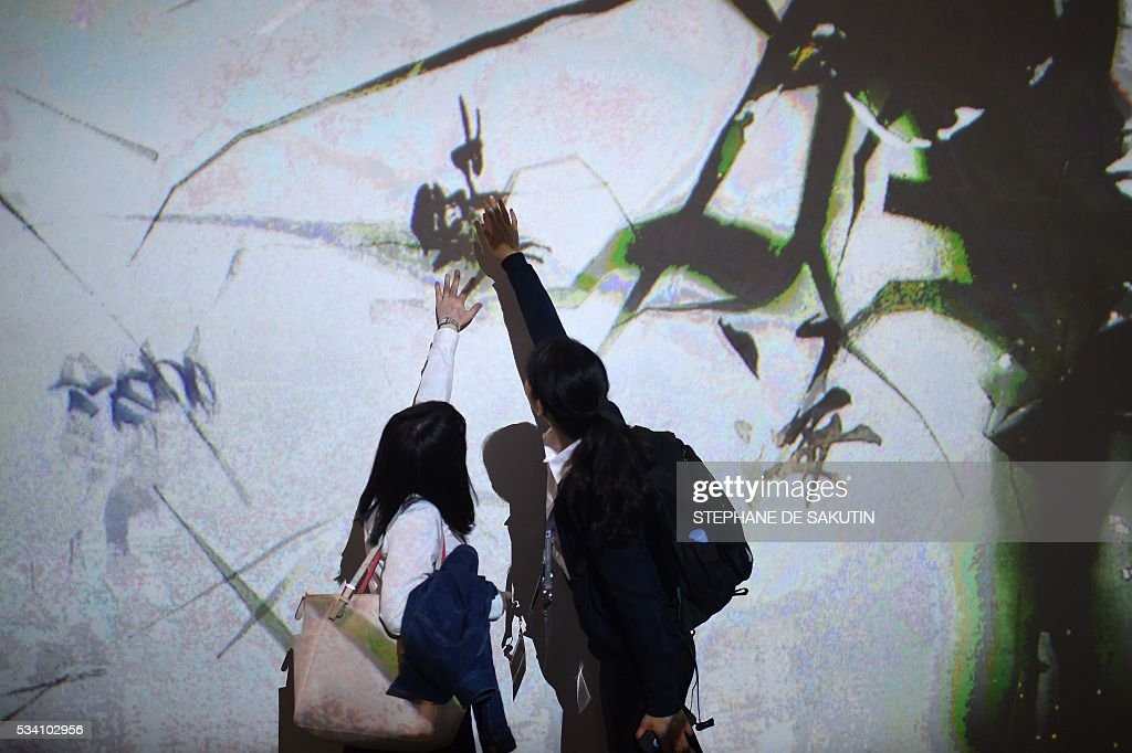 People touch an interactive wall at the International Media Centre in Ise city, Mie prefecture on May 25, 2016, ahead of the G7 summit. / AFP / STEPHANE
