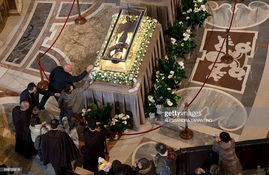 People touches the transparent coffin of St Padre Pio on display in St Peter's basilica, on February 6, 2016 in Vatican. Pio was revered during his lifetime (1887-1968) and his popularity has continued to grow since his death, particularly in Italy, where mini-statues and pictures of the mystical Capuchin friar are ubiquitous. / AFP / POOL / Alessandra Tarantino
