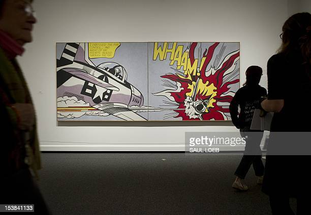 People tour a retrospective of US pop artist Roy Lichtenstein including his 1963 canvas 'Whaam' at the National Gallery of Art in Washington on...