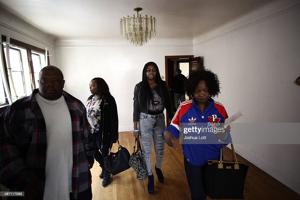 People tour one of twelve homes being auctioned off in the East English Village neighborhood April 27, 2014 in Detroit, Michigan. The city of Detroit and the Detroit Land Bank will auction off 12 homes starting May 5. One home will be auctioned off per day with an opening bid of $1,000.