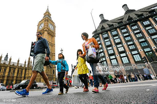 People tourists and a family with two children are walking over a street crossing at the landmark of Big Ben on August 7 2012 in London England...