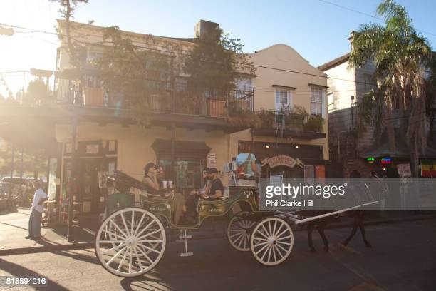 People tourists riding on a horse and carriage through the streets in the French Quarter arty shot golden light flare New Orleans Louisiana USA