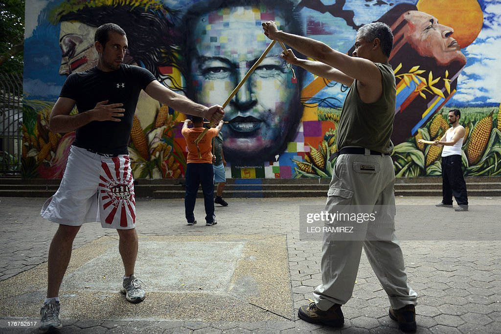 People train stick fight in front of a mural depicting late Venezuelan former President Hugo Chavez in Caracas on August, 18, 2013. AFP PHOTO/Leo RAMIREZ