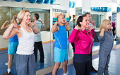 Positive friendly smiling people training in a gym doing pilates